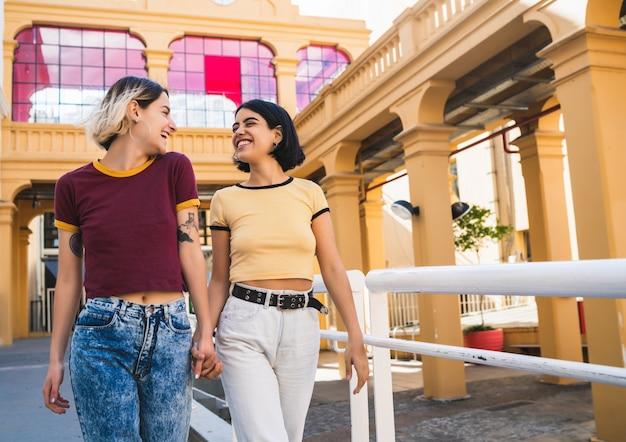 一緒に時間を過ごし、屋外でデートをしている素敵なレズビアンのカップルの肖像画。
