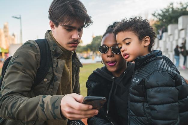 屋外の公園で楽しんで、リラックスして、携帯電話を使用して楽しんでいる素敵な混血民族家族の肖像画。