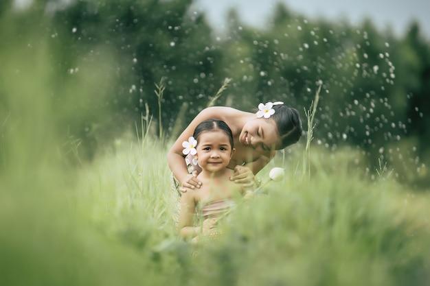 사랑스러운 여동생과 태국 전통 드레스의 젊은 여동생의 초상화와 초원에 앉아 그녀의 귀에 흰 꽃을 넣어, 그들은 함께 미소, 형제 사랑 개념, 복사 공간