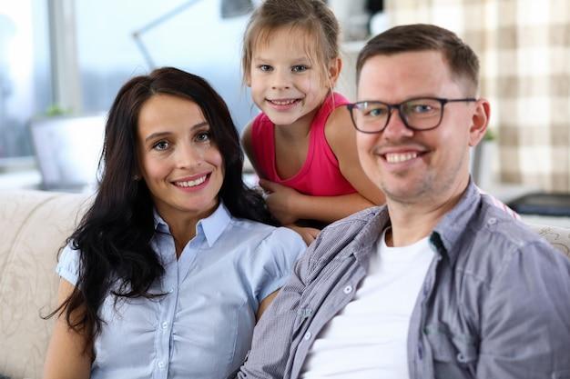 一緒に時間を過ごす素敵な笑顔の家族の肖像画。幸せな母、父、ソファーに座っていると嬉しそうに見ている小さな子供。子供の頃と親のコンセプト