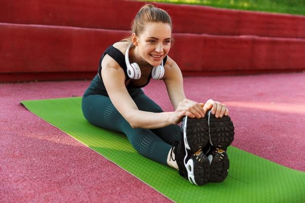 녹색 공원에서 운동하는 동안 운동복을 입은 사랑스러운 스포티 여성의 초상화