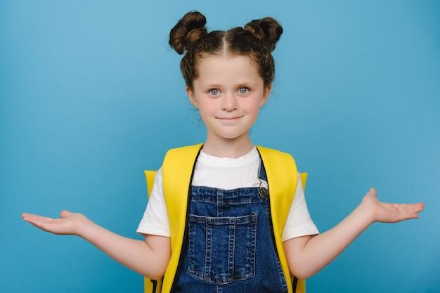 사랑스러운 작은 여학생의 초상화는 노란색 배낭을 메고 빈 공간을 들고 두 손바닥 팔을 들고 스튜디오에서 파란색 배경 위에 고립된 포즈를 취하며 빛나는 미소를 짓고 있습니다.