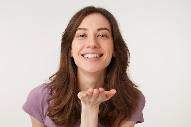 Портрет прекрасной сладкой женщины с современной прической, дует воздушный поцелуй с улыбкой