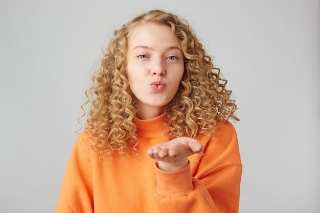 Портрет прекрасной милой молодой девушки с современной прической, дует воздушный поцелуй