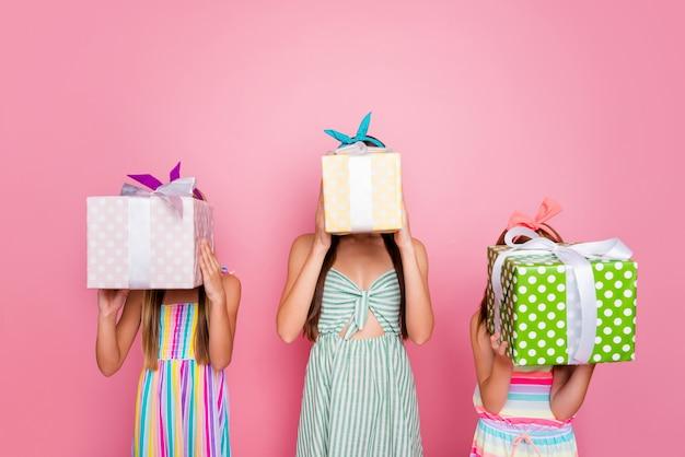 Портрет милых винтажных девушек, скрывающих свои лица, держащих полученные пакеты в повязках на юбке, изолированных на розовом фоне