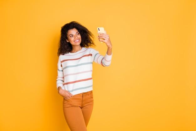 Портрет милой волнистой девушки с помощью цифрового телефона, делающей селфи