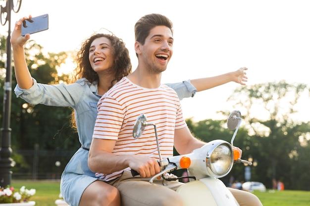 젊은 남자와 함께 도시 거리를 통해 오토바이를 타고있는 동안 스마트 폰에 셀카를 복용 사랑스러운 여자의 초상화