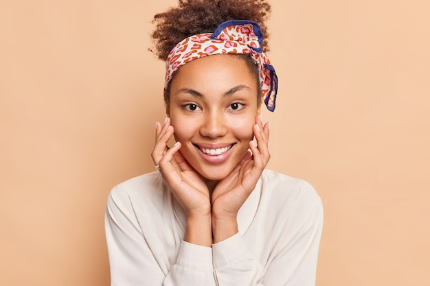Портрет прекрасной женщины трогает лицо, нежно широко улыбается, имеет идеальные белые зубы, носит повязку на голову, а рубашка счастливо смотрится спереди, изолированно от бежевой стены