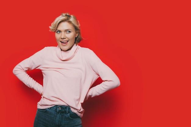 사랑스러운 젊은 금발의 여자의 초상화는 멀리 빨간 스튜디오 배경에 고립 된 그녀의 혀를 보여주는 엉덩이에 손으로 분홍색 옷을 입고 있습니다.