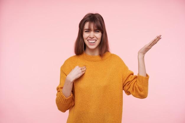 Портрет прекрасной молодой голубоглазой темноволосой дамы, хмурящейся, смущенно поднимающей ладонь, одетой в горчичный вязаный свитер, позируя над розовой стеной
