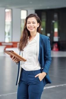 Портрет прекрасной молодой бизнес-леди, стоящей в офисном зале с цифровым планшетом в руках