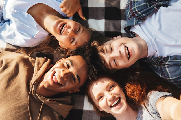 사랑스러운 젊은 친구 남자와 여자의 초상화 웃고, 야외 서클에서 담요에 누워