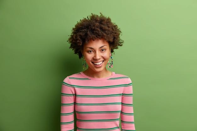 カメラでフレンドリーな幸せな表情で素敵な若いルックスの肖像画は、緑の鮮やかな壁にさりげなく隔離された服を着て良い気分になっているポジティブな感情を表現しています