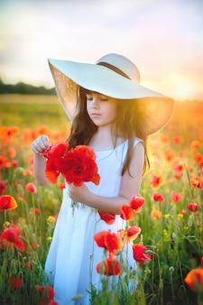 フィールドの背景にポーズをとって手にケシの花を持つ素敵なロマンチックな少女の肖像画。麦わら帽子をかぶっています。