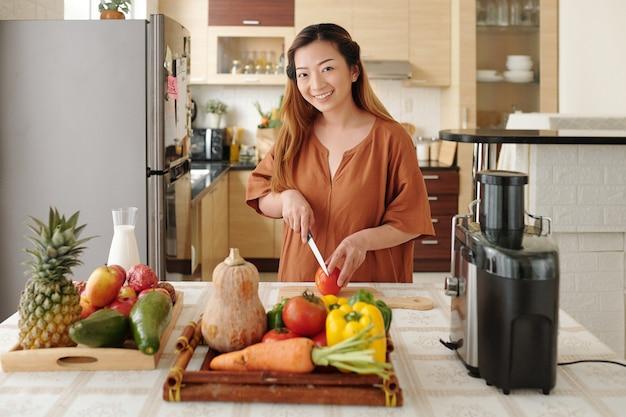 Портрет прекрасной молодой женщины, режущей помидоры, готовя здоровое блюдо на ужин