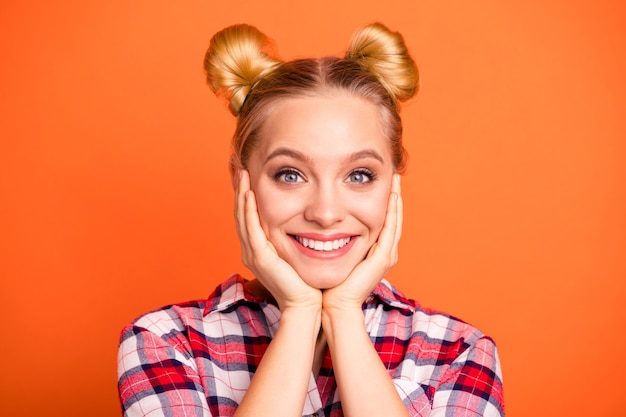 Портрет прекрасной молодой женщины, одетой в клетчатую рубашку, изолированную на оранжевом
