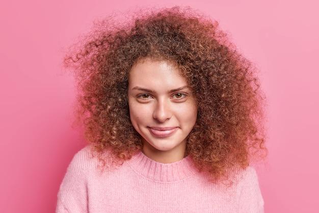 Портрет прекрасной молодой женщины с вьющимися густыми волосами смотрит прямо, приятно улыбается, имеет здоровую кожу, носит повседневный джемпер, изолированный над розовой стеной. концепция выражения человеческого лица