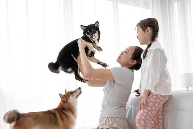 Портрет милой семьи с коричневыми симпатичными двумя собаками расслабиться и отдохнуть на кровати в спальне. у них есть домашние животные в качестве компаньона и они избавляют от одиночества.