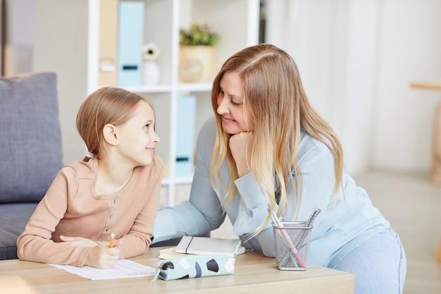 Портрет любящей взрослой матери, смотрящей на милую маленькую девочку, делающую домашнюю работу во время учебы дома в уютном интерьере, копией пространства