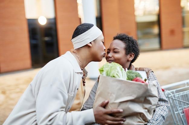 Портрет любящей афро-американской женщины, целующей сына за то, что он вместе помогает с продуктовыми покупками