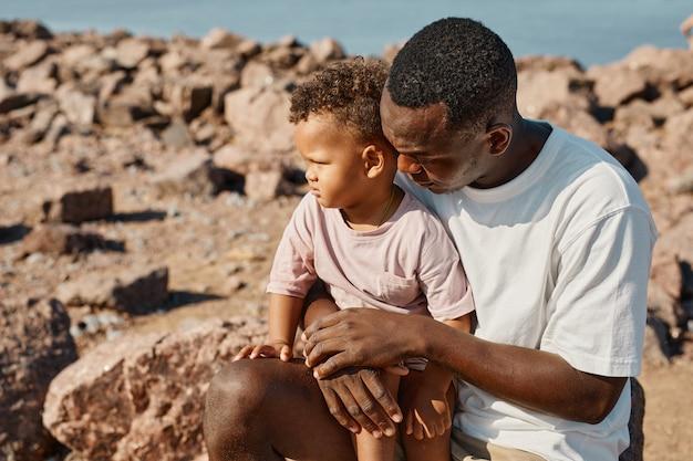ビーチのコピースペースでかわいい息子と遊ぶ愛情のあるアフリカ系アメリカ人の父の肖像画