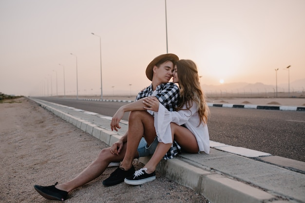 夏の週末に市内を旅行した後、高速道路の隣に座っている間、カップルがキスを愛するの肖像画。夕暮れ時の道の近くで休んで、彼女のボーイフレンドを優しく抱きしめるうれしそうな長い髪の女性