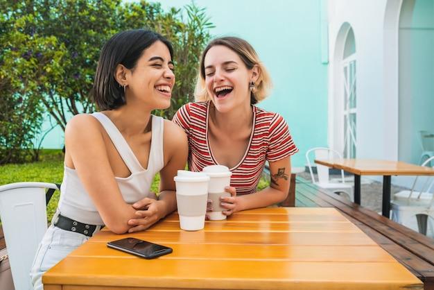 一緒に楽しい時間を過ごし、コーヒーショップでデートをしている愛するレズビアンのカップルの肖像画。