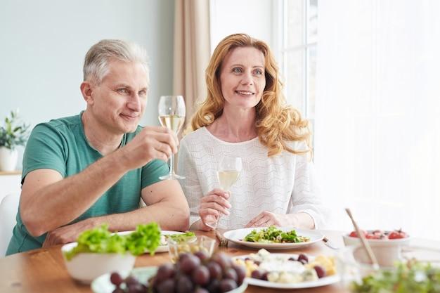 Портрет любящей зрелой пары, поднимающей бокалы с шампанским, наслаждаясь романтическим ужином дома, копией пространства