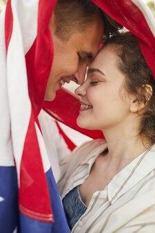 愛情を込めて抱きしめ、アメリカの国旗に覆われた笑顔の若いカップルを愛する肖像画