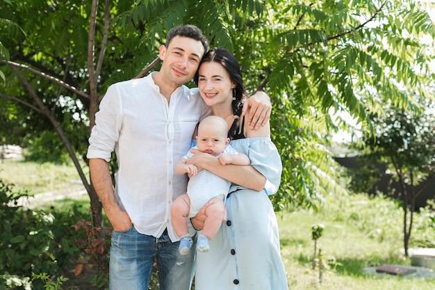 공원에 서있는 그들의 아기와 함께 사랑하는 젊은 부부의 초상