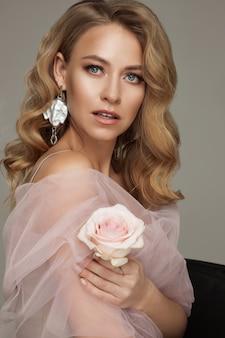 ピンクのバラを保持している完璧なメイクのポーズで豪華なブロンドの女性の肖像画