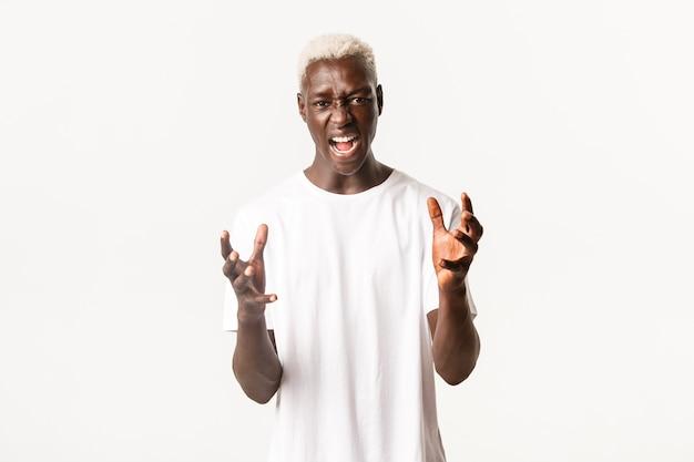 Портрет безумного афро-американского блондина, сжимая руки и ругаясь, крича сердито, в ярости на белом фоне.