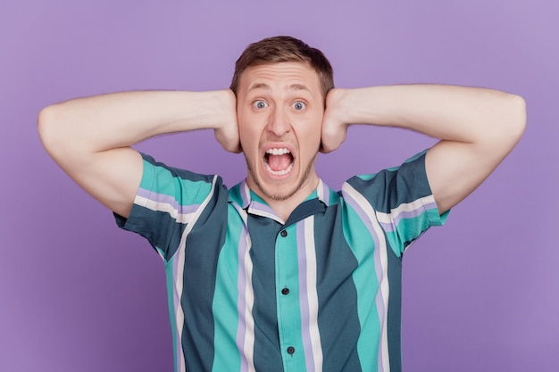 화가 난 화가 난 남자의 초상화는 귀를 닫고 보라색 배경에 입을 벌리고 소리친다
