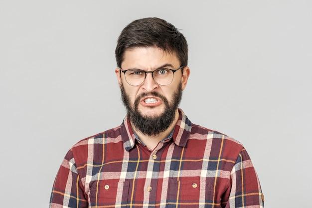 Портрет сумашедшего сердитого молодого мужского гнева и ярости. изолированные на серый