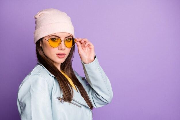 壮大なゴージャスな十代の少女の肖像画は彼女のスペックに触れ、紫色の背景の上に分離されたクールな服装カジュアルスタイルの服を感じます
