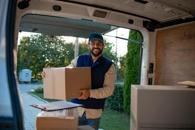 Портрет почтальона, держащего пакеты у своего фургона.