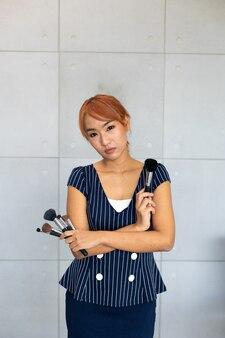 메이크업 브러쉬와 메이크업 아티스트 아시아 여자의 초상화.
