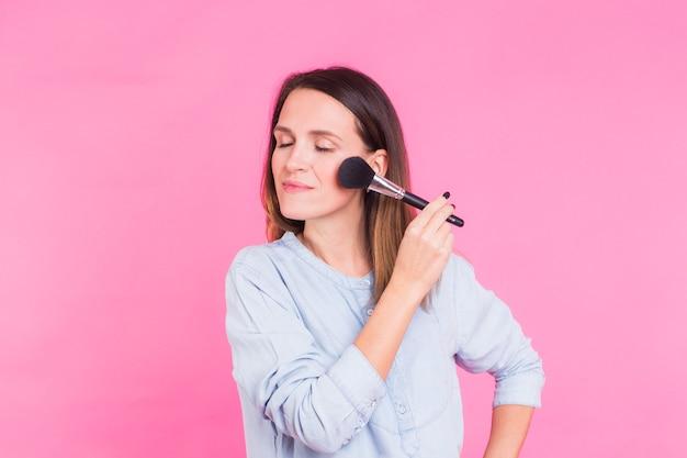 ピンクの壁にブラシでメイクアップアーティストの肖像画。