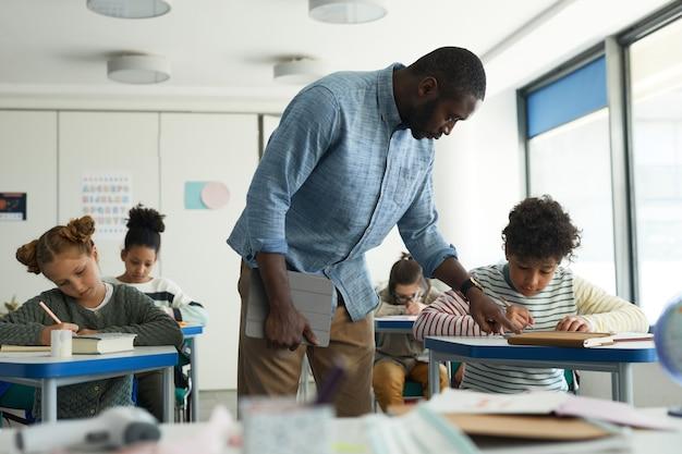 Портрет учителя-афроамериканца-мужчины, помогающего детям в школьном классе