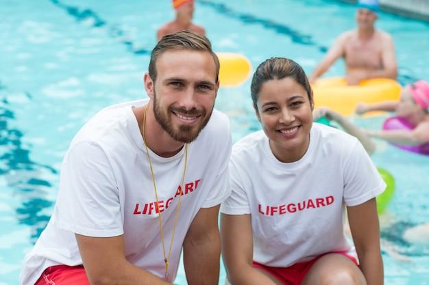 Портрет мужчин и женщин-спасателей, сидящих на корточках у бассейна