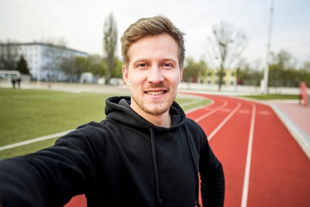 Портрет мужчины спортсмен, принимая селфи на мобильном телефоне на красной гоночной трассе