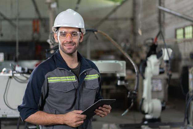 産業工場の検査ロボットアーム溶接機のホールドタブレットを笑顔の男性の自動化エンジニアの肖像画
