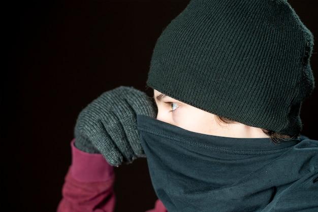 Портрет мужчины-бандита в черных бандановых перчатках и шляпе, изолированных на темном фоне b