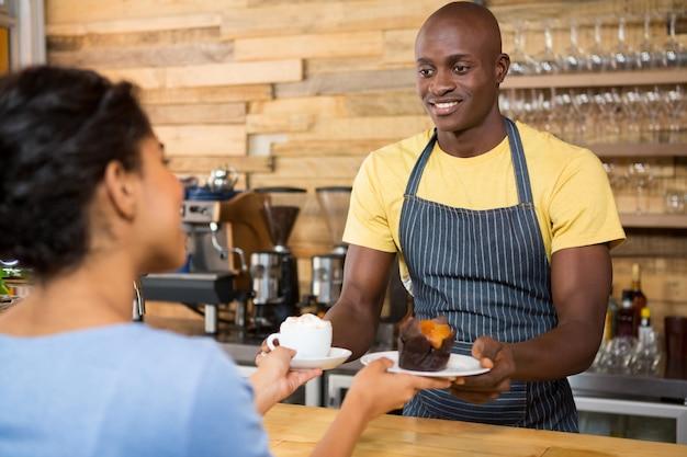 カフェで女性の顧客にコーヒーとデザートを提供する男性のバリスタの肖像画