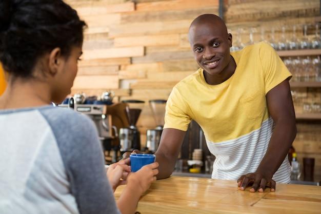 カフェで女性の顧客にコーヒーを提供する男性のバリスタの肖像画