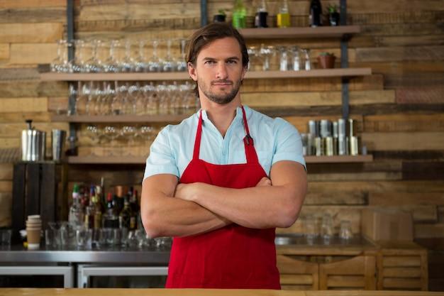 コーヒーショップで交差した男性のバリスタ立っている腕の肖像画