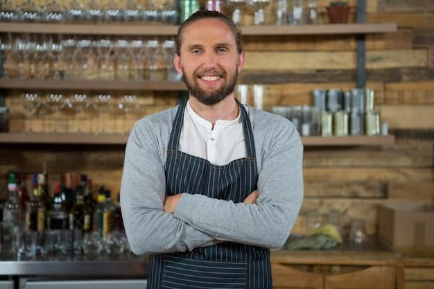 Портрет мужчины бариста стоя скрещенными руками в кафе