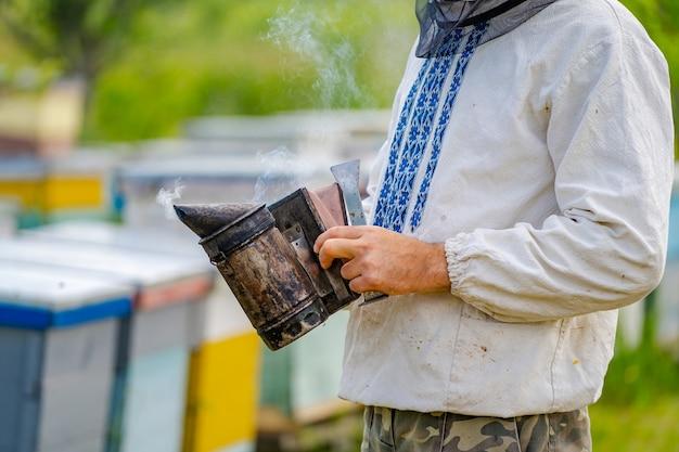 배경에 두드러기가 있는 남성 양봉가의 초상화. 보호복을 입고 있습니다. 양봉장. 손에 꿀벌 흡연자.