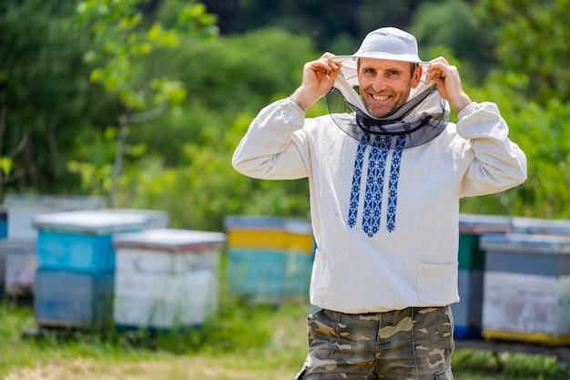 背景にじんましんを持つ男性のビーキーパーの肖像画。保護服を着用してください。養蜂場。