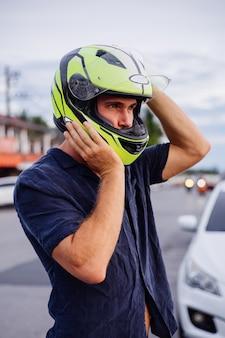 일몰 시간에 태국에서 바쁜 도로의 측면에 노란색 헬멧에 남성 자전거 타는 사람의 초상화